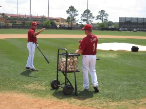 Stubby Clapp tossing a ball to infield instructor Tom Lawless as he hits grounders