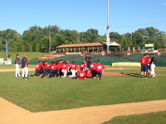 The team takes a knee on the infield to listen to instructions from manager Ed Romero