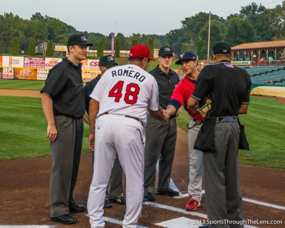 'Cats manager Ed Romero and Spikes manager Oliver Marmol meet with the umpires at home plate.