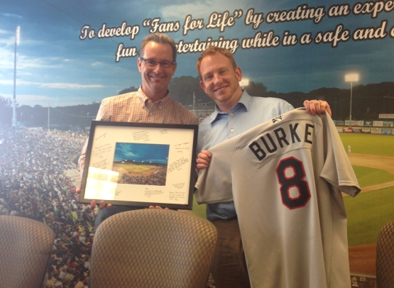 "ValleyCats GM Rick Murphy presents Ryan with a #8 jersey for his eight years with the ValleyCats, and a framed photo of ""The Joe"" signed by members of the front office."