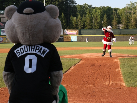 Santa Clause throwing out the first pitch to his elf Buddy!